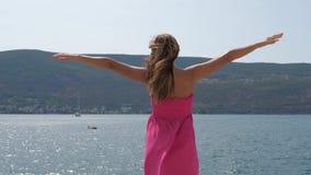 Μια γυναίκα σε ένα φόρεμα που διαδίδεται οπλίζει στις πλευρές και επάνω προς τη The Sun στη θάλασσα απόθεμα βίντεο