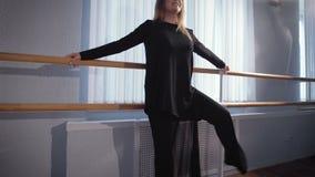 Μια γυναίκα σε μια καλή διάθεση στη μηχανή μπαλέτου στην αίθουσα για το χορό Ζυμώνει τα πόδια και το podgotoavlivaetsya για απόθεμα βίντεο