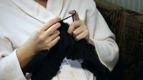 Μια γυναίκα σε μια ρόμπα συμμετείχε στο πλέξιμο φιλμ μικρού μήκους