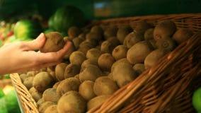 Μια γυναίκα σε μια υπεραγορά σε ένα φυτικό ράφι, αγοράζει τα λαχανικά και τα φρούτα στενό απομονωμένο καρπός ακτινίδιο ανασκόπηση φιλμ μικρού μήκους