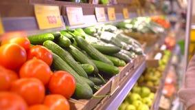 Μια γυναίκα σε μια υπεραγορά σε ένα φυτικό ράφι, αγοράζει τα λαχανικά και τα φρούτα Η γυναίκα επιλέγει τα αγγούρια κίνηση αργή φιλμ μικρού μήκους
