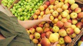 Μια γυναίκα σε μια υπεραγορά σε ένα φυτικό ράφι, αγοράζει τα λαχανικά και τα φρούτα Το άτομο επιλέγει τα μήλα Σε αργή κίνηση, 4k φιλμ μικρού μήκους