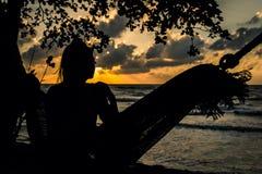 Μια γυναίκα σκιαγραφιών σε μια αιώρα Στοκ Εικόνες