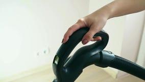 Μια γυναίκα σκουπίζει το πάτωμα με ηλεκτρική σκούπα Κινηματογράφηση σε πρώτο πλάνο του χεριού και μιας λαβής ηλεκτρικών σκουπών απόθεμα βίντεο