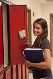 Μια γυναίκα σπουδαστής ανοίγει ένα ντουλάπι. Στοκ Φωτογραφία