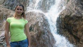 Μια γυναίκα στέκεται σε ένα υπόβαθρο ενός καταρράκτη Γρήγορος καταρράκτης που μειώνει το βράχο Όμορφο χαμογελώντας κορίτσι δίπλα  φιλμ μικρού μήκους