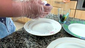 Μια γυναίκα στα αυγά χρωμάτων γαντιών φιλμ μικρού μήκους