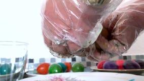 Μια γυναίκα στα αυγά χρωμάτων γαντιών απόθεμα βίντεο