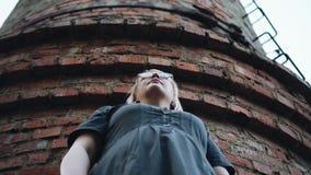 Μια γυναίκα στα γυαλιά στέκεται κάτω από έναν μακρύ σωλήνα τούβλου συμπαθητικός πυροβολισμός κινηματογραφήσεων σε πρώτο πλάνο απόθεμα βίντεο