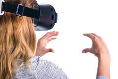 Μια γυναίκα στα γυαλιά εικονικής πραγματικότητας κρατά ένα φανταστικό αντικείμενο Στοκ Φωτογραφίες