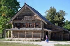 Μια γυναίκα στα εθνικά ρωσικά ενδύματα πηγαίνει σε ένα παραδοσιακό ρωσικό αρχαίο ξύλινο σπίτι Στοκ Εικόνες