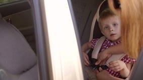 Μια γυναίκα στερεώνει τις ζώνες μιας παιδιών ασφαλείας στο κάθισμα αυτοκινήτων φιλμ μικρού μήκους