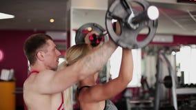 Μια γυναίκα στη γυμναστική κάνει τις ασκήσεις με τη βοήθεια ενός εκπαιδευτικού ικανότητας φιλμ μικρού μήκους