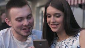 Μια γυναίκα στις φωτογραφίες μιας ανδρών προσοχής σε ένα smartphone ένας θερινός καφές απόθεμα βίντεο