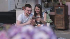 Μια γυναίκα στις φωτογραφίες μιας ανδρών προσοχής σε ένα smartphone ένας θερινός καφές φιλμ μικρού μήκους