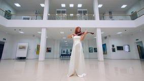 Μια γυναίκα στο άσπρο βιολί παιχνιδιού φορεμάτων σε ένα μουσείο απόθεμα βίντεο