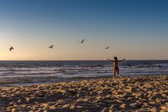 Μια γυναίκα στο κόκκινο μαγιό στην παραλία στοκ εικόνα