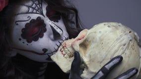 Μια γυναίκα στο makeup ενός μεξικάνικου κρανίου φιλά παθιασμένα ένα αιματηρό κρανίο, μια εικόνα αποκριών απόθεμα βίντεο