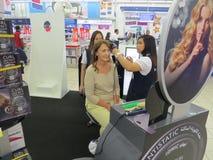 Μια γυναίκα συμμετέχει σε μια διαφημιστική καμπάνια Ο πωλητής κοριτσιών κάνει τις μπούκλες της με την τρίχα styler στη λεωφόρο το στοκ φωτογραφίες