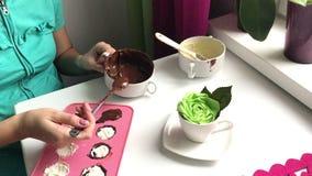 Μια γυναίκα σφραγίζει μια στάρπη συμπληρώνοντας τη μορφή σιλικόνης με τη λειωμένη σοκολάτα Μαγειρεύοντας επιδόρπιο φιλμ μικρού μήκους