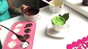 Μια γυναίκα σφραγίζει μια στάρπη συμπληρώνοντας τη μορφή σιλικόνης με τη λειωμένη σοκολάτα Μαγειρεύοντας επιδόρπιο απόθεμα βίντεο