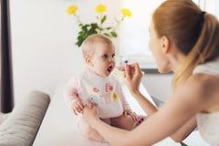 Μια γυναίκα ταΐζει ένα μωρό με ένα κουτάλι Ένα παιδί κάθεται σε έναν πίνακα στην κουζίνα και τρώει με την ευχαρίστηση στοκ φωτογραφία με δικαίωμα ελεύθερης χρήσης
