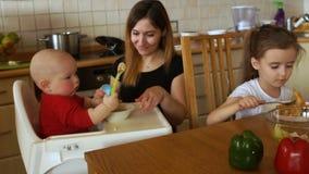 Μια γυναίκα ταΐζει δύο παιδιά στην κουζίνα Το παιδί παίζει στην προεδρία με τα κουτάλια και δεν θέλει να φάει Η νοσοκόμα φιλμ μικρού μήκους