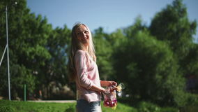 Μια γυναίκα ταΐζει τα πουλιά στο πάρκο απόθεμα βίντεο