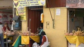 Μια γυναίκα τεμαχίζει επάνω στο κοτόπουλο σε ένα δευτερεύον κατάστημα οδών σε Cusco φιλμ μικρού μήκους
