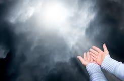 Μια γυναίκα την επεκτείνει παραδίδει την προσευχή στον ουρανό, από τον οποίο μέσω των σκοτεινών σύννεφων φαίνεται ακτίνα του ligh στοκ φωτογραφία με δικαίωμα ελεύθερης χρήσης