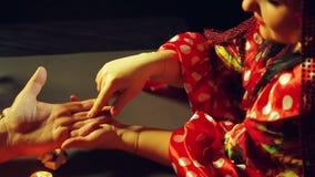 Μια γυναίκα τσιγγάνων σε μια αίθουσα τύχη-αφήγησης από το φως ιστιοφόρου αναρωτιέται έναν άνδρα από το χέρι φιλμ μικρού μήκους