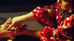 Μια γυναίκα τσιγγάνων σε μια αίθουσα τύχη-αφήγησης από το φως ιστιοφόρου αναρωτιέται έναν άνδρα από το χέρι απόθεμα βίντεο