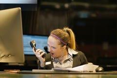 Μια γυναίκα-υποδοχή ορκίζεται με τον πελάτη τηλεφωνικώς στοκ φωτογραφία