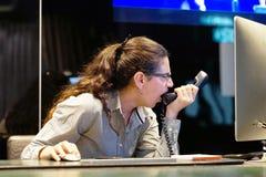 Μια γυναίκα-υποδοχή ορκίζεται με τον πελάτη τηλεφωνικώς στοκ εικόνες