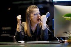 Μια γυναίκα-υποδοχή ορκίζεται με τον πελάτη τηλεφωνικώς στοκ φωτογραφίες με δικαίωμα ελεύθερης χρήσης