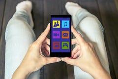 Μια γυναίκα χρησιμοποιεί τα κοινωνικά δίκτυα με ένα κινητό τηλέφωνο στοκ εικόνα