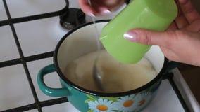 Μια γυναίκα χύνει τη ζάχαρη σε ένα δοχείο και γλείφει το αγάρ που αραιώνεται στο νερό Για την κατασκευή marshmallow απόθεμα βίντεο