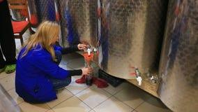 Μια γυναίκα χύνει το κρασί σε ένα μπουκάλι από ένα βαρέλι Υπόγειος θάλαμος κρασιού φιλμ μικρού μήκους