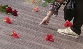 Μια γυναίκα ψάχνει το όνομα των συγγενών της στον αναμνηστικό τάφο τοίχων μνήμης στη Μαγιόρκα ευρέως στοκ φωτογραφία με δικαίωμα ελεύθερης χρήσης