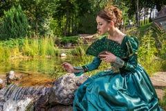 Μια γυναίκα όπως μια πριγκήπισσα σε ένα εκλεκτής ποιότητας φόρεμα στο πάρκο νεράιδων Στοκ φωτογραφία με δικαίωμα ελεύθερης χρήσης