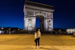 Μια γυναίκα Arc de Triomphe στο Παρίσι, Γαλλία τη νύχτα Στοκ Φωτογραφίες