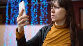 Μια γυναίκα blogger χρησιμοποιεί το τηλέφωνο στο εσωτερικό δίπλα στα μπλε ηλεκτρικά φω'τα απόθεμα βίντεο
