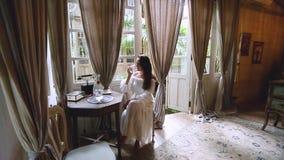 Μια γυναίκα brunette σε ένα άσπρο φόρεμα κάθεται σε έναν πίνακα και πίνει το νερό Εκλεκτής ποιότητας εσωτερικό του δωματίου στο υ απόθεμα βίντεο