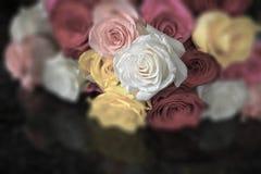 Μια δέσμη πολλών χρωματισμένων τριαντάφυλλων μαζί στο μαύρο γρανίτη στοκ εικόνα με δικαίωμα ελεύθερης χρήσης