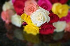 Μια δέσμη πολλών χρωματισμένων τριαντάφυλλων μαζί στο μαύρο γρανίτη στοκ εικόνα