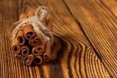 Μια δέσμη της κανέλας έδεσε με ένα σχοινί σε ένα ξύλινο υπόβαθρο στοκ εικόνα