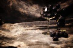 Μια δέσμη των μαύρων σταφυλιών που γεμίζουν wineglass στο γκρίζο στούντιο backdr στοκ φωτογραφία με δικαίωμα ελεύθερης χρήσης