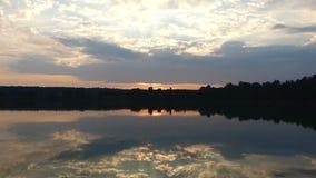 Μια δασική λίμνη με το καθαρό νερό, την ομαλή επιφάνεια, τις ξύλινες ακτές και το θαυμάσιο ηλιοβασίλεμα απόθεμα βίντεο
