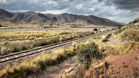 Μια διαδρομή σιδηροδρόμων που οδηγεί μέσω του ξηρού τοπίου του νότιου Περού Στοκ Φωτογραφία