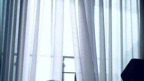 Μια διαφανής κουρτίνα στο παράθυρο, που κινείται ήπια από τον αέρα Φως του ήλιου 4K απόθεμα βίντεο